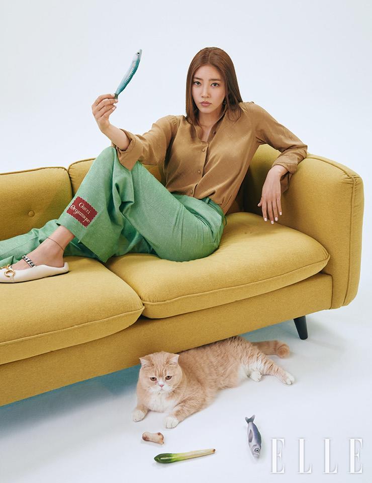 베이지 브라운 셔츠와 라벨 포인트 민트 팬츠, 체인 디테일의 화이트 플랫 슈즈는 모두 Gucci.
