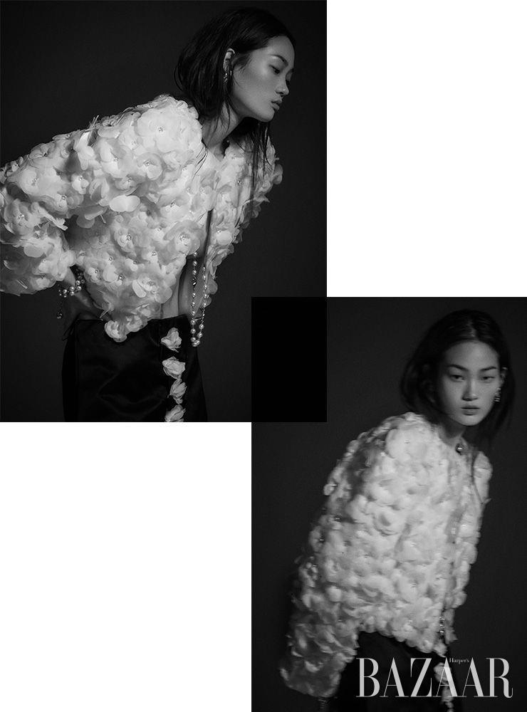 카멜리아 모티프 재킷, 새틴 소재 스커트, 귀고리, 진주 목걸이, 팔찌는 모두 Chanel.
