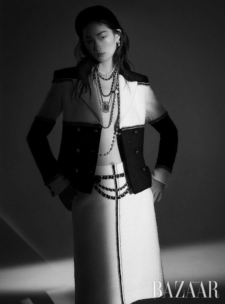 컬러 블록 트위드 재킷, 스커트, 헤어밴드, 귀고리, 여러 줄로 레이어드된 진주 목걸이, 향수 병 모티프 목걸이, 체인 벨트는 모두 Chanel.
