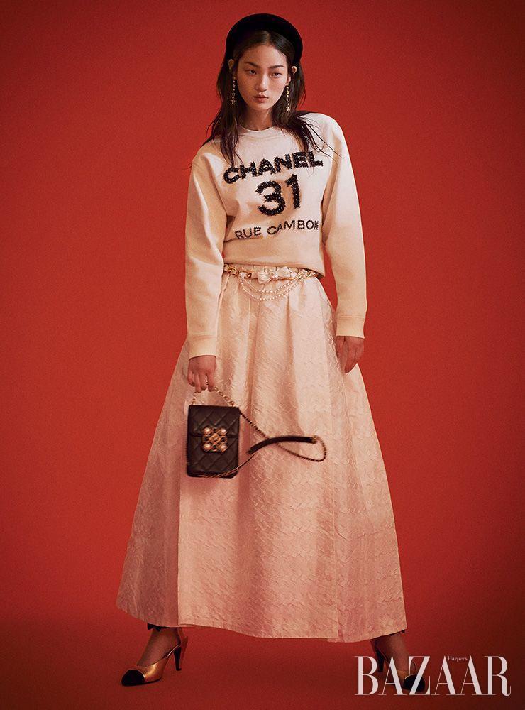 스웨트셔츠, 스커트, 벨벳 헤어밴드, 드롭 귀고리, 진주 장식 체인 벨트, 체인 플랩 백, 슈즈는 모두 Chanel.