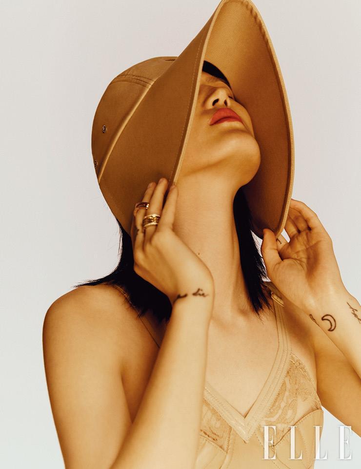 독특한 셰이프의 모자는 65만원, 코르셋 톱은 가격 미정, 모두 Burberry. 중지에 낀 로즈골드 블랙 세라믹 세팅 링은 2백만원대, 약지에 낀 옐로골드 다이아몬드 세팅 링은 9백만원대, 모두 Bvlgari.