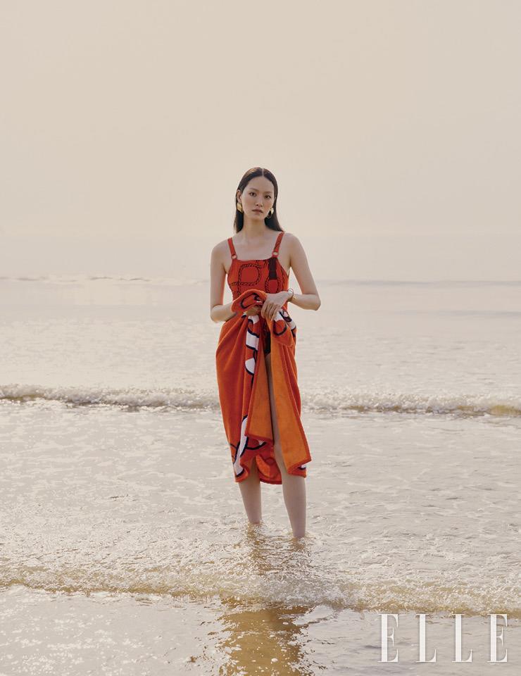 오렌지 컬러 원피스 수영복과 비치 타월, 레더 브레이슬렛은 가격 미정, 모두 Hermès. 골드 이어링은 가격 미정, Louis Vuitton.