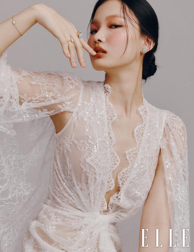 레이스 로브 드레스는 Alon Livné White by Heritique New York, 터쿠아즈가 세팅된 투 헤드 링과 화이트 마더 오브 펄이 세팅된 링, 브레이슬렛은 모두 Boucheron.
