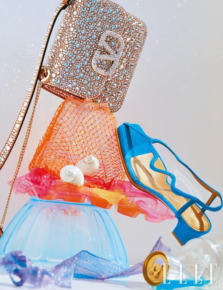 크리스털을 빼곡히 장식한 숄더백은 가격 미정, Valentino Garavani. 소라 모티프의 이어 클립은 가격 미정, Prada. 블루 컬러의 곡선 디테일이 돋보이는 PVC 샌들은 38만8천원, Recto.