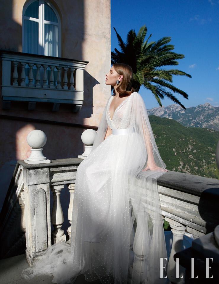 어깨에서 시작하는 주름 장식이 우아한 드레스는 Elisabetta Polignano. 이어링은 Sharra Pagano. 화이트 펌프스는 Aquazzura.
