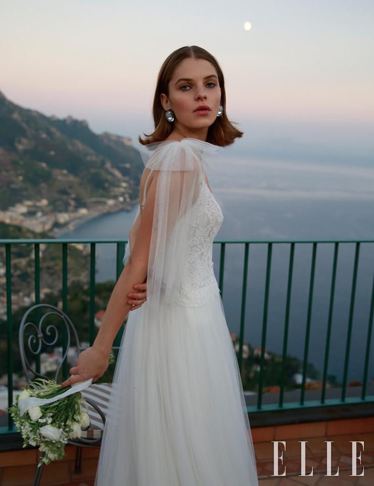 어깨의 리본 장식이 귀여운 드레스는 Aire Barcelona. 볼드한 이어링은 Sharra Pagano. 부케는 Malafronte Fiori.