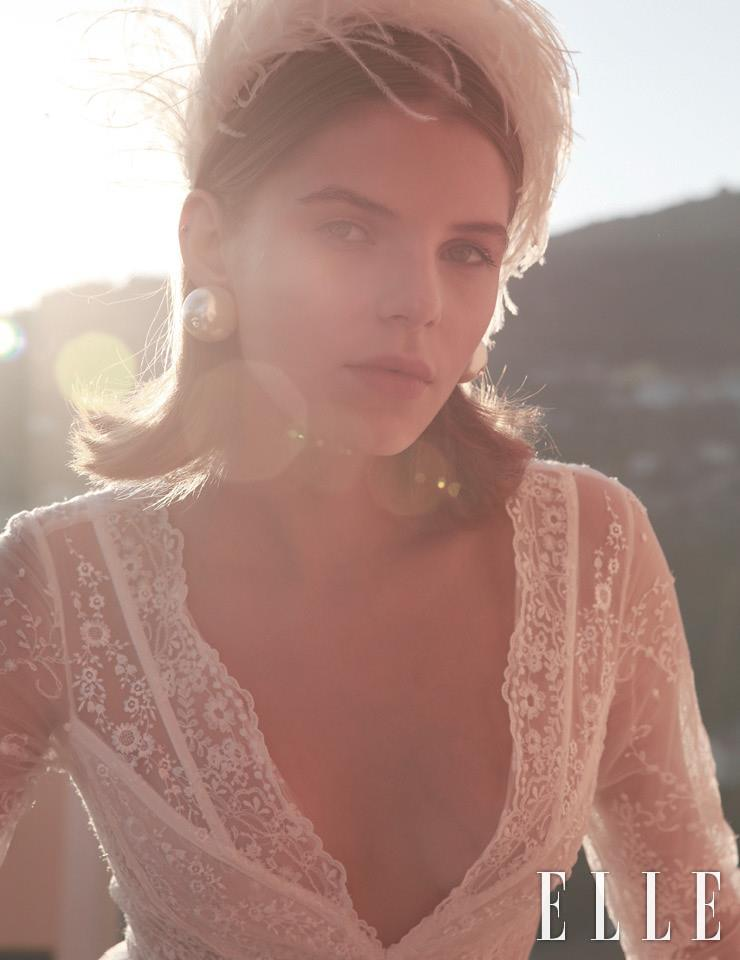 레이스 드레스는 Le Spose di Gio. 깃털 장식의 헤어밴드는 Flapper. 진주 이어링은 Alessandra Rich.