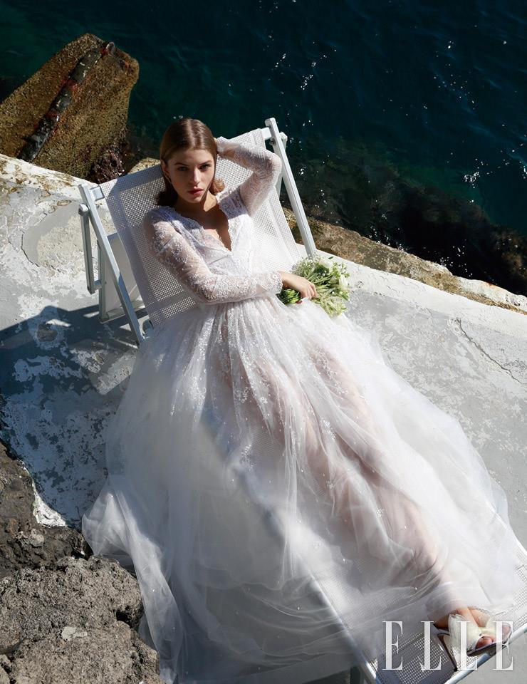 잔잔한 레이스 소재의 V 네크라인 드레스는 Le Spose di Gio. 이어링은 The Attico. 부케는 Malafronte Fiori. 리본 장식의 앵클 스트랩 샌들은 Jimmy Choo.