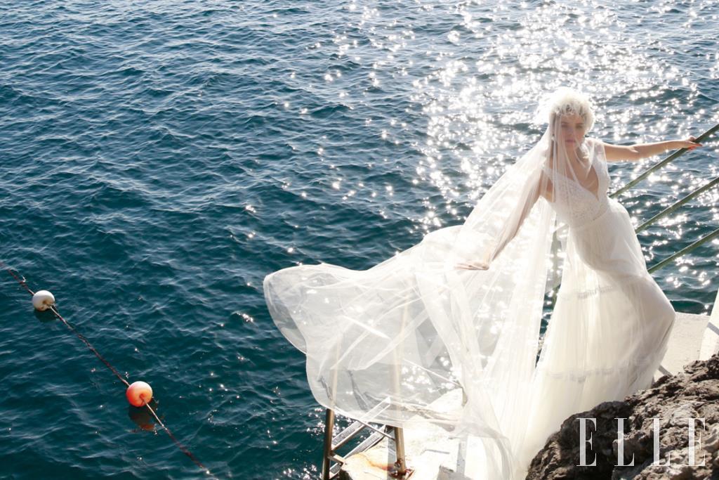 크리스털 장식의 딥 v 네크라인 드레스와 롱 베일은 모두 Rosa Clara'. 깃털 장식의 헤어밴드는 Flapper. 옐로골드 링은 Dior Joaillerie.