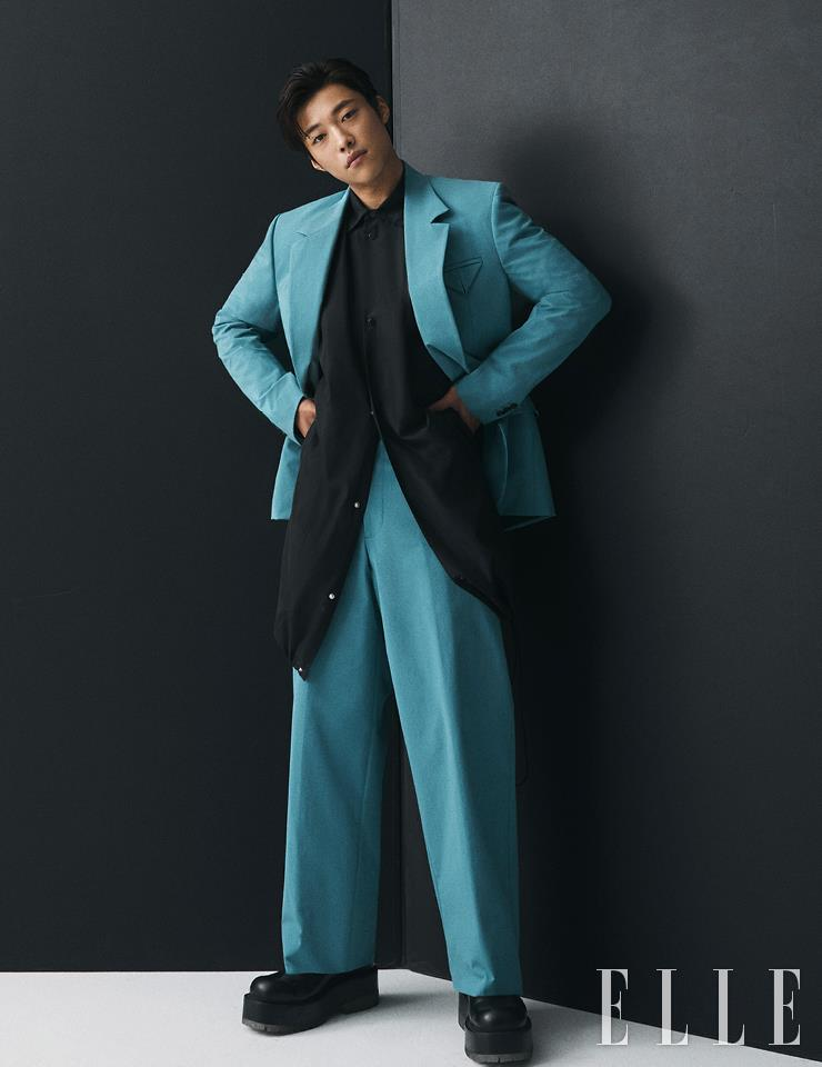 밑단 스트링 디테일의 블랙 셔츠와 블루 수트, 슈즈는 모두 Bottega Veneta.