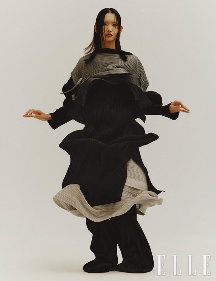 매듭 장식의 그레이 톱과 안에 레이어드해서 입은 블랙 드레스, 풍성한 그레이 플리츠스커트, 블랙 팬츠는 모두 Pleats Please Issey Miyake.