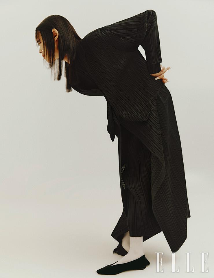 블랙 플리츠 드레스와 롱 블랙 코트, 그 위에 레이어드한 블랙 베스트는 모두 Pleats Please Issey Miyake.