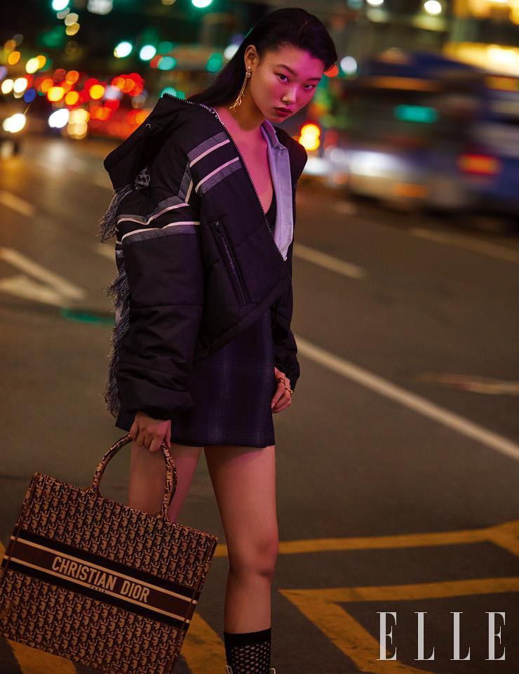 패딩 아우터웨어와 셔츠, 블랙 브라톱, 체크 패턴의 미니스커트, 골드 드롭 이어링, 왼손에 착용한 골드 링, 벨벳 오블리크 북 토트백, 피시넷 타이츠는 모두 Dior.