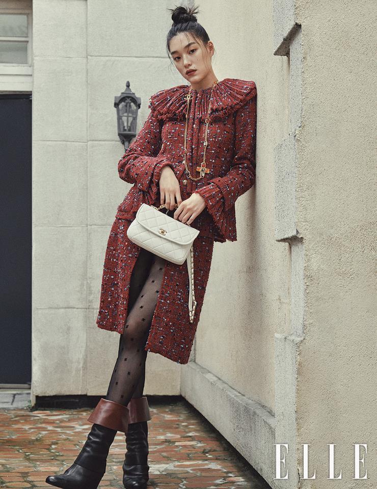 유니크한 칼라가 돋보이는 트위드 재킷과 미디스커트, 레이어드한 쇼츠, 컬러 스톤 장식의 골드 네크리스, 가죽 부츠, 램스킨 소재의 화이트 백과 타이츠는 모두 Chanel.