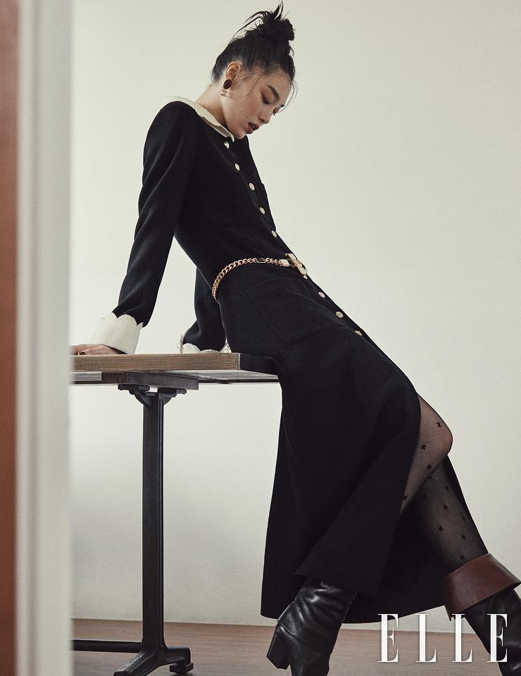 로맨틱한 칼라의 블랙 롱 드레스와 골드 체인 벨트, 로고 장식의 이어링, 가죽 부츠, 타이츠는 모두 Chanel.