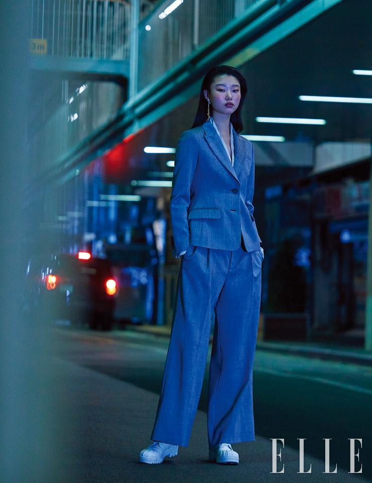 그레이 수트 재킷과 와이드 팬츠, 셔츠, 화이트 레더 부츠, 골드 드롭 이어링은 모두 Dior.