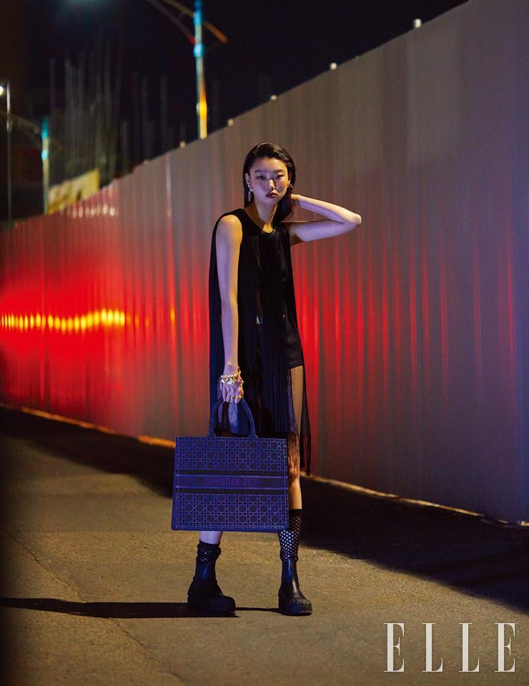프린지 디테일의 블랙 드레스와 이너 웨어로 착용한 브리프, 피시넷 삭스, 첼시 부츠, 물고기 모티프의 골드 이어링, 로고 형태의 골드 이어링, 다양한 참을 장식한 진주 브레이슬렛, 골드 링, 벨벳 카나주 북 토트백은 모두 Dior.