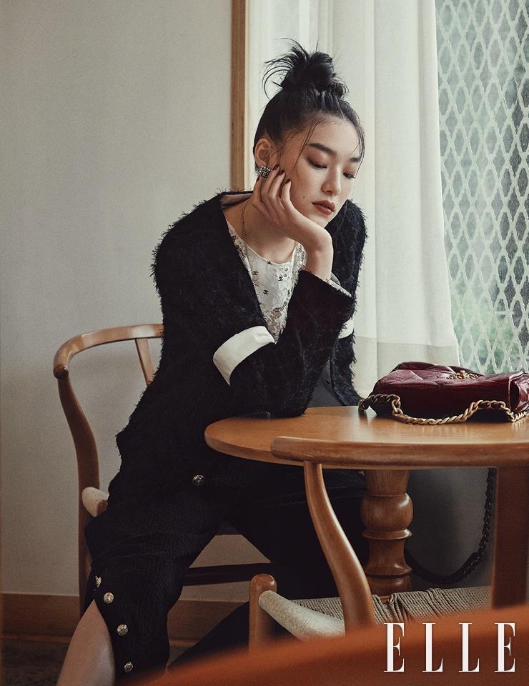 판타지 트위드 소재의 블랙 재킷과 레이스 톱, 단추가 달린 팬츠, 로고 장식의 사각 이어링, 롱 네크리스, 테이블 위에 놓인 카프스킨 소재의 '19' 백은 모두 Chanel.