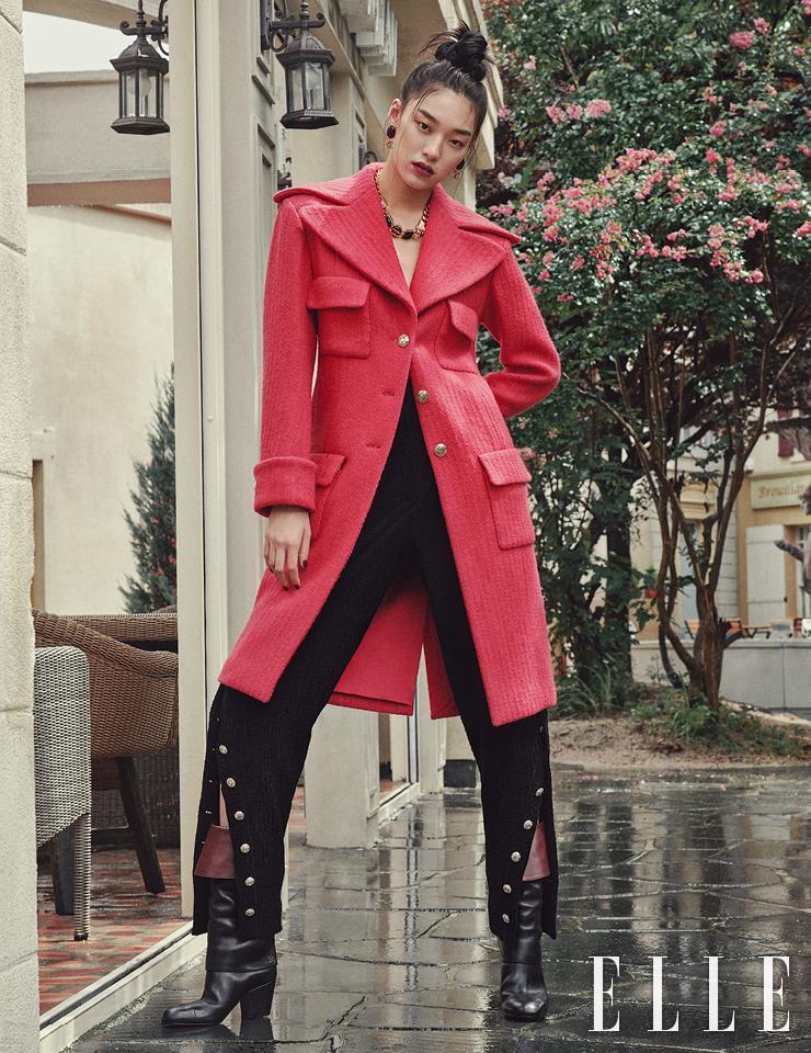 울 트위드 소재의 코트와 단추가 달린 팬츠, 가죽 부츠, 로고 장식 이어링, 체인 네크리스는 모두 Chanel.