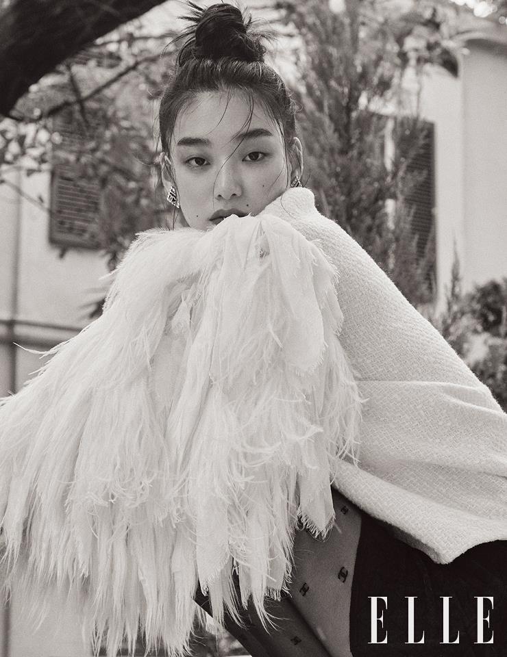 풍성한 깃털 장식의 트위드 재킷과 미니스커트, 로고 장식의 사각 이어링, 타이츠는 모두 Chanel.