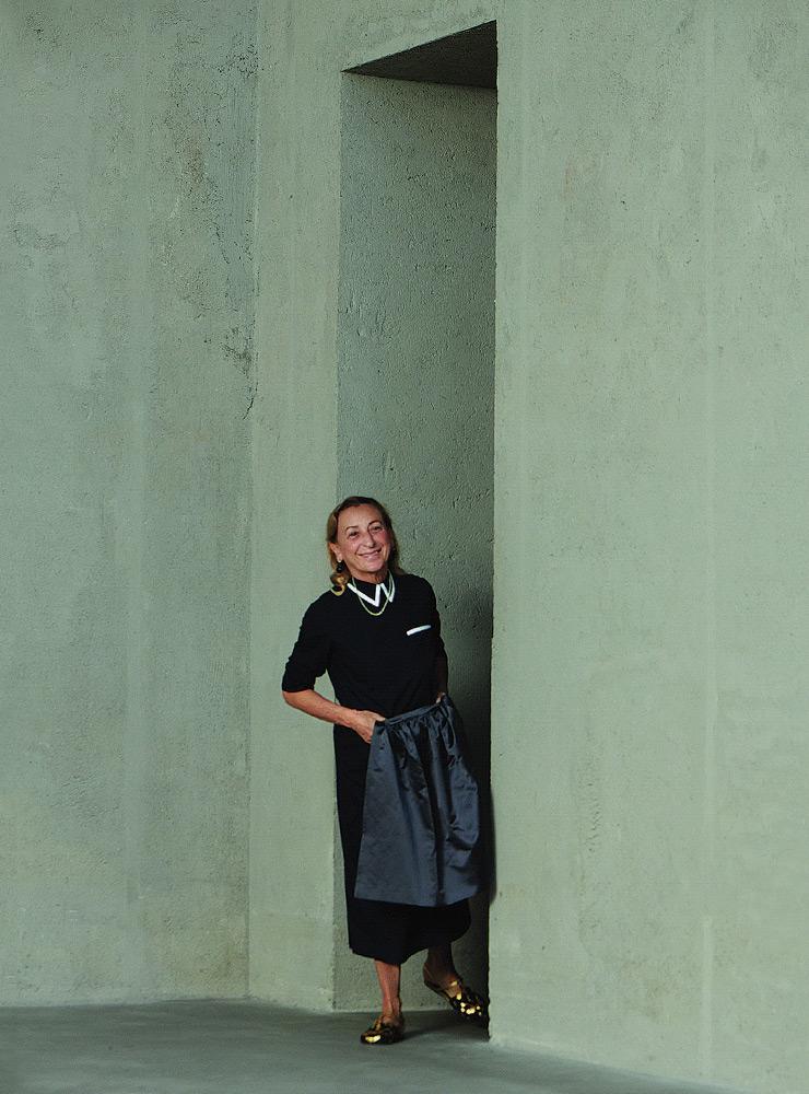 미우치아 프라다가 그녀가 사랑해 마지않는 에이프런 모티프 옷을 입고 멀티플 뷰즈 2021 S/S 쇼에서 수줍게 피날레 인사를 하고 있다.