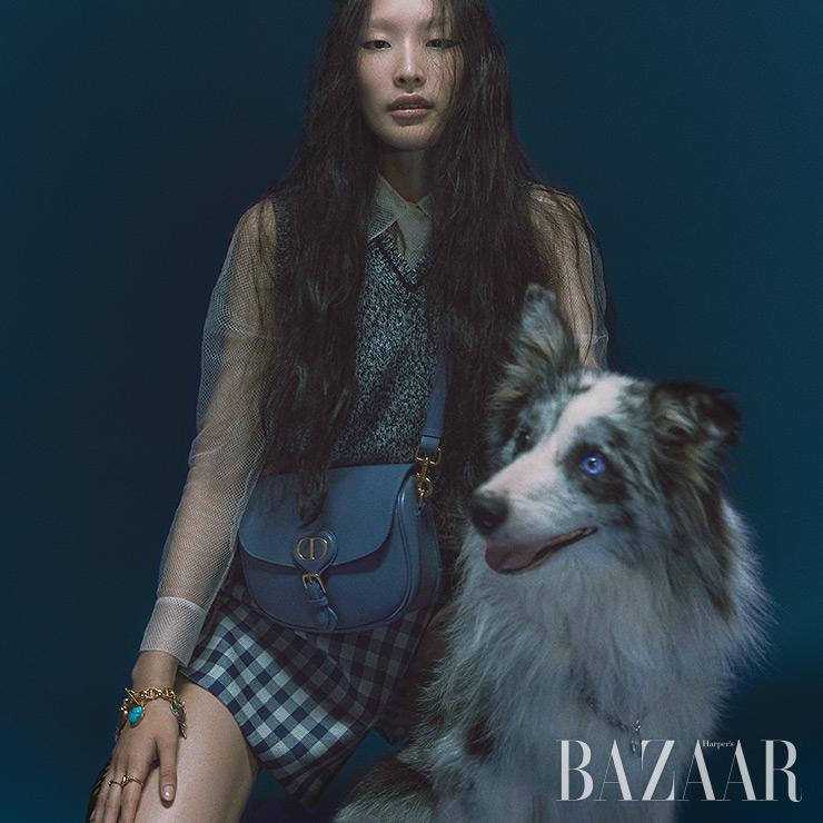메시 셔츠, 베스트, 퀼로트 팬츠, 타이, 미디엄 사이즈의 블루 '디올 바비' 백, 팔찌, 반지는 모두 Dior.