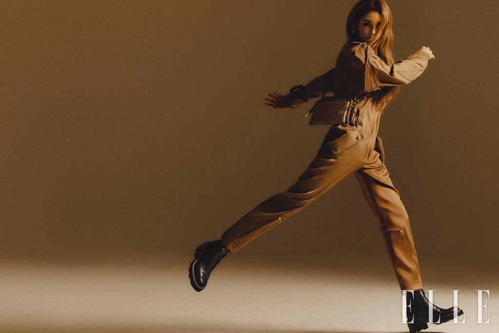 점프수트와 투박한 앵클부츠, 백팩 모양의 브레이슬렛, 모노그램 패턴의 파우치 LV3 백과 이어링은 모두 Louis Vuitton.