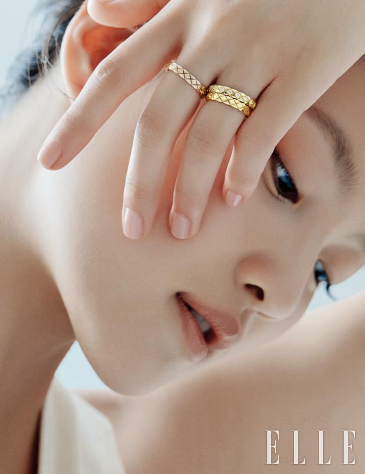 약지에 레이어드한 옐로골드 코코 크러쉬 미니 링과 다이아몬드 세팅의 옐로골드 코코 크러쉬 미니 링, 중지의 베이지골드 코코 크러쉬 미니 링은 모두 Chanel Fine Jewelry.