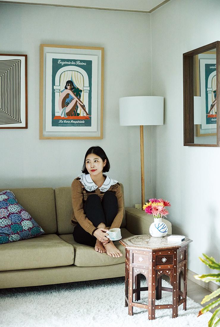 거실에 앉아 있는 김현아. 벽에는 파리 오리지널 포스터 가게에서 산 베르나르 빌모의 포스터가 걸려 있다. 협탁은 인도 벼룩시장에서 어머니가 구입한 것.