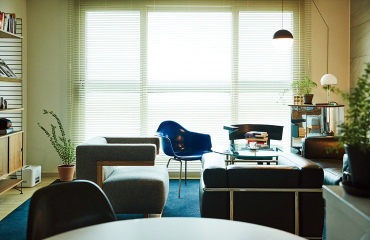 푸른 카펫이 거실 전체에 깔려 있다. LC2 의자, 텍타의 F51 그로피우스 암체어 사이에 파란 임스 플라스틱 암체어가 공간에 포인트를 준다.