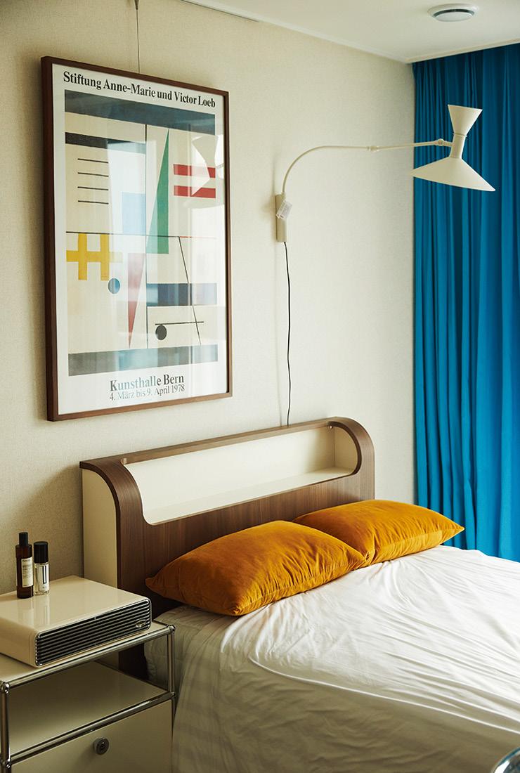빈티지 느낌의 에이스 침대가 놓인 침실. 벽에 걸린 조명은 르 코르뷔지에가 디자인한 랑프 드 마르세유.