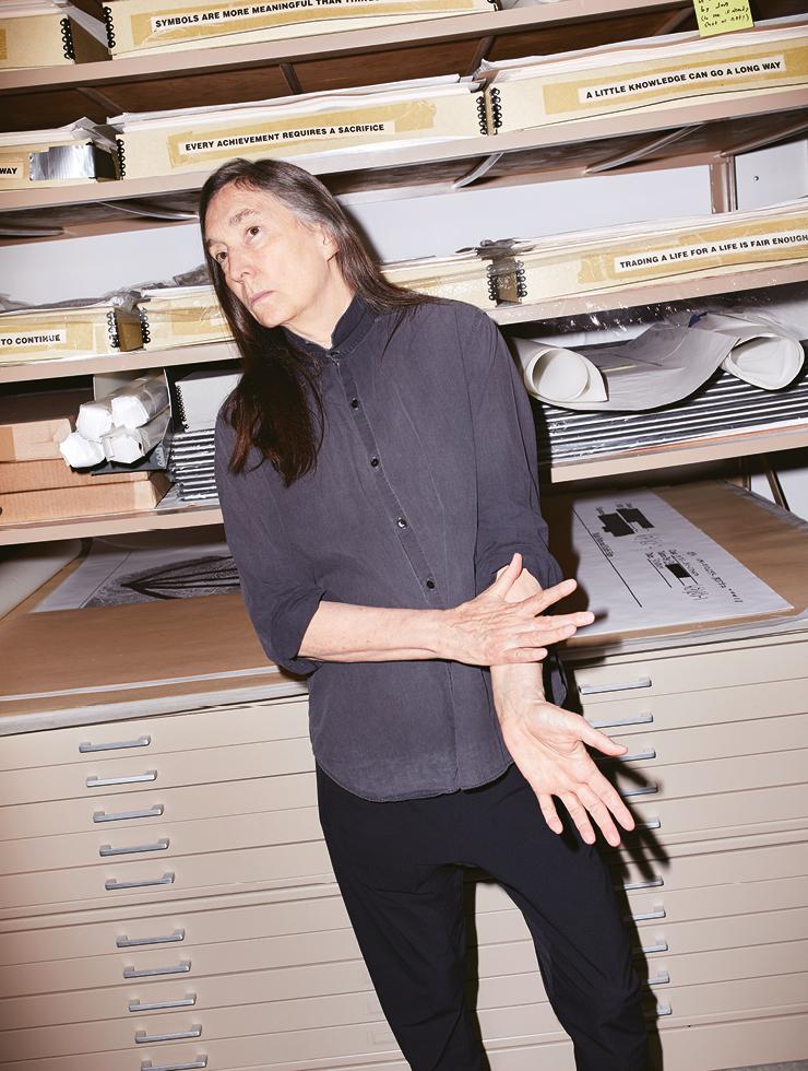 제니 홀저가 자신의 스튜디오에서 무언가를 응시한다 .