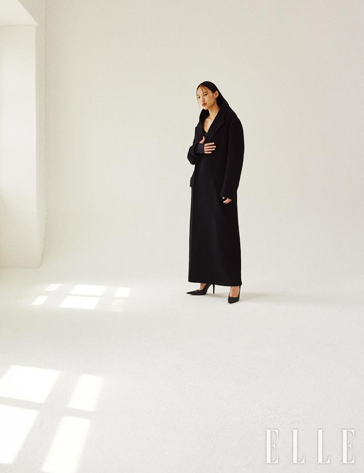 조형적인 실루엣의 블랙 맥시 코트와 랩 디테일의 톱, 스틸레토 힐은 가격 미정, 모두 Balenciaga.