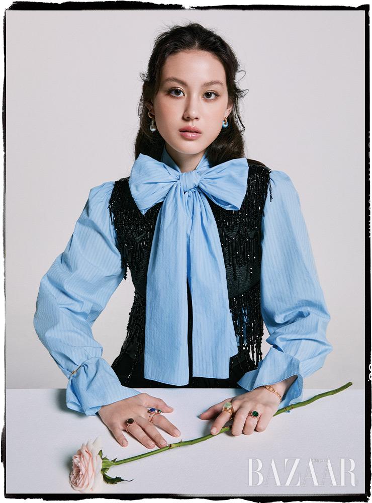 보타이 블라우스는 45만원대 Eenk. 베스트는 Prada. 귀고리는 45만원 Timeless Pearly by BOONTHESHOP. 팔찌는 Dior. 왼손 검지에 착용한 반지는 45만원 Jem & Pebbles. 나머지 반지는 모두 RoseeDor.